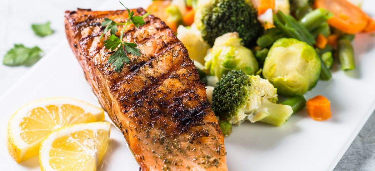 Fish and vegetables menu. Grilled salmon fish fillet with vegetables mix on white plate. Close up.